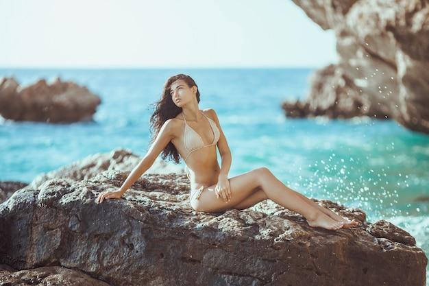 Retrato de mulher jovem e bonita na selvagem praia rochosa.