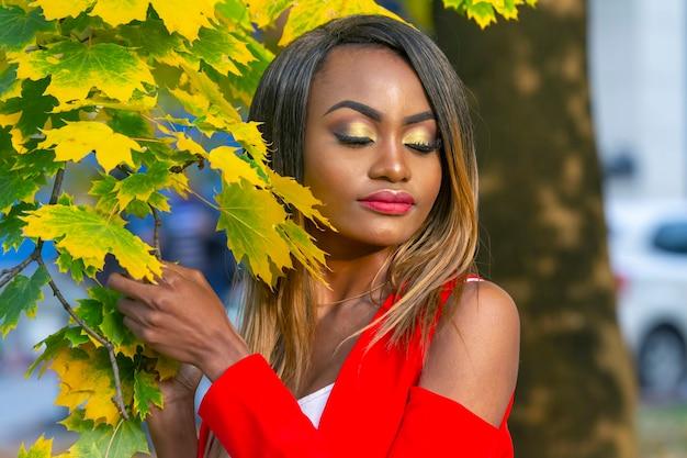 Retrato de mulher jovem e bonita nas folhas de outono