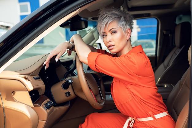 Retrato de mulher jovem e bonita no carro novo - ao ar livre