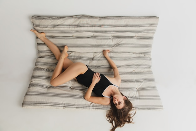 Retrato de mulher jovem e bonita no colchão cinza em estúdio. se divertindo, feliz, corpo inteiro