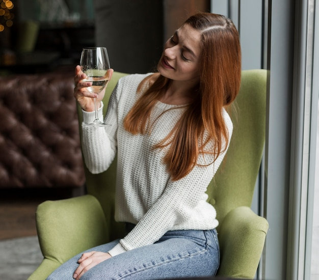 Retrato de mulher jovem e bonita olhando para um copo de vinho