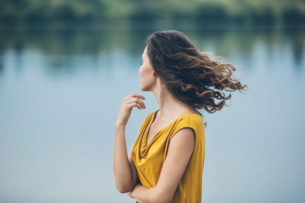 Retrato de mulher jovem e bonita perto do lago em um vestido brilhante