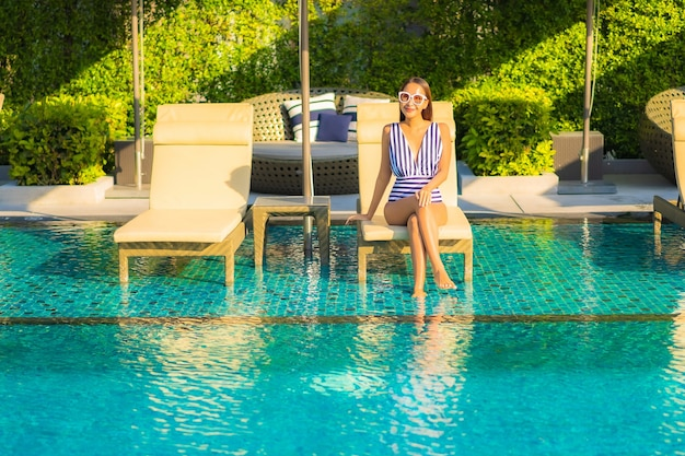 Retrato de mulher jovem e bonita relaxando sorriso lazer nas férias ao redor da piscina em hotel resort