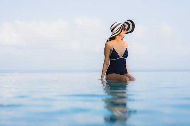 Retrato de mulher jovem e bonita relaxante ao redor da piscina no hotel resort