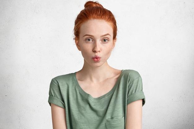 Retrato de mulher jovem e bonita sardenta mantém os lábios arredondados, parece com expressão engraçada, faz careta, vestida casualmente, isolada sobre o branco