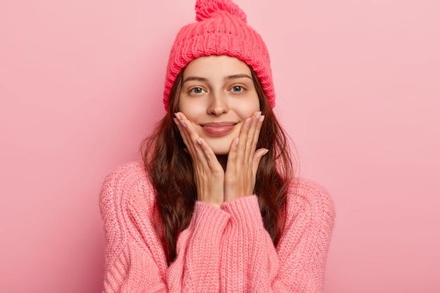 Retrato de mulher jovem e bonita sorri agradavelmente, mantém as duas mãos nas bochechas, olha com alegria para a câmera, tem aparência relaxada, usa um suéter e chapéu de inverno de malha, modelos internos sobre parede rosa do estúdio