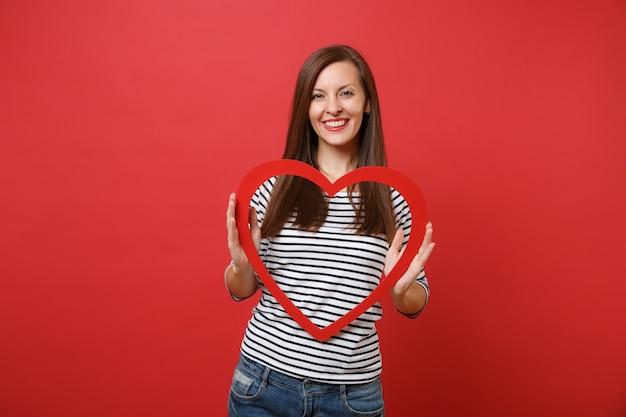 Retrato de mulher jovem e bonita sorridente em roupas listradas casuais, segurando um grande coração de madeira vermelho isolado no fundo da parede vermelha brilhante. emoções sinceras de pessoas, conceito de estilo de vida. simule o espaço da cópia.