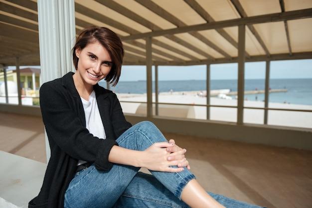 Retrato de mulher jovem e bonita sorridente, sentada em caramanchão à beira-mar