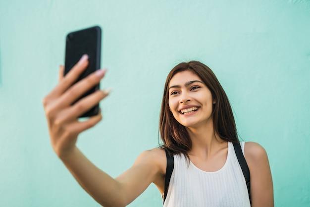 Retrato de mulher jovem e bonita tirando selfies com seu telefone mophile ao ar livre. tecnologia e conceito urbano.