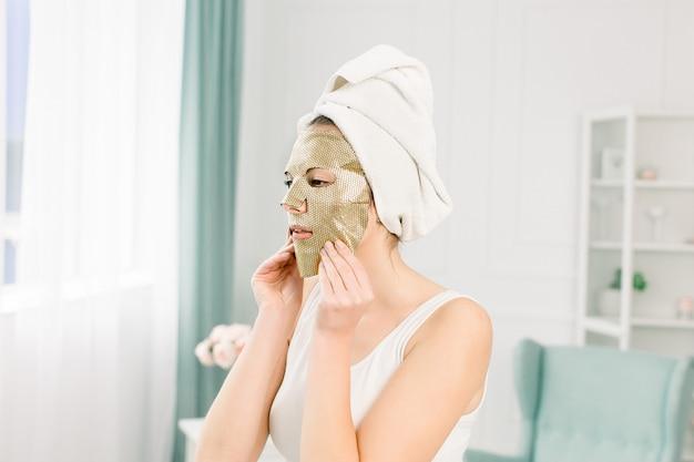 Retrato de mulher jovem e bonita toalha branca na cabeça com maquiagem nude e máscara de ouro de papel cosmético no rosto.