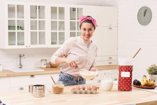 Retrato de mulher jovem e bonita tomando café na cozinha.