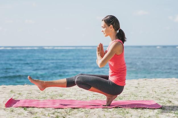Retrato de mulher jovem e desportiva fazendo meditação ao ar livre