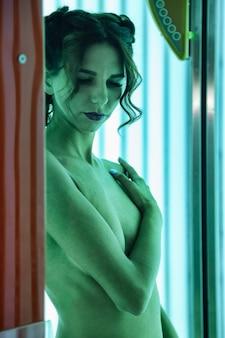 Retrato de mulher jovem e elegante bonita desfrutando de um bronzeado no solário moderno. mulher jovem e saudável no solário vertical, obtém prazer e goza. conceito de estilo de vida saudável e pele bonita e bem cuidada