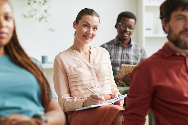 Retrato de mulher jovem e elegante sorrindo e tomando notas enquanto está sentado na platéia em um seminário de treinamento ou conferência de negócios no escritório