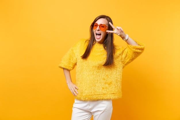 Retrato de mulher jovem e feliz animada com suéter de pele e óculos coração laranja mostrando sinal de vitória isolado em fundo amarelo brilhante. emoções sinceras de pessoas, conceito de estilo de vida. área de publicidade.