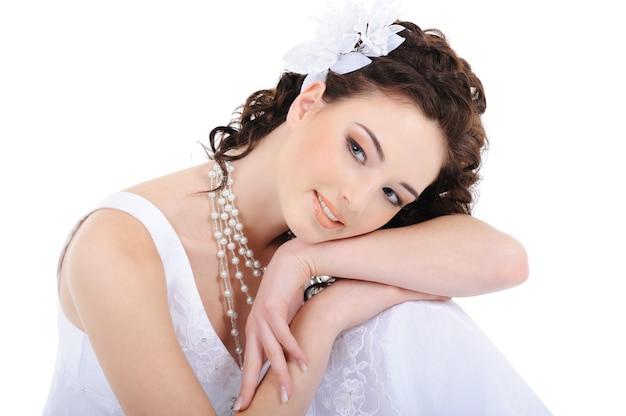 Retrato de mulher jovem e fresca em um vestido de noiva branco com cabelos cacheados