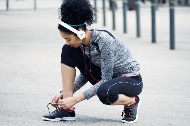 Retrato de mulher jovem em forma e desportiva, amarrando o cadarço antes de uma corrida.