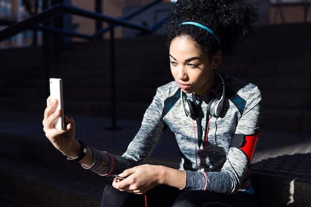 Retrato de mulher jovem em forma e desportiva, usando seu telefone celular.
