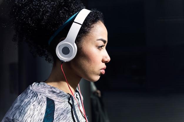 Retrato de mulher jovem em forma e desportivo, ouvindo música com o telemóvel.