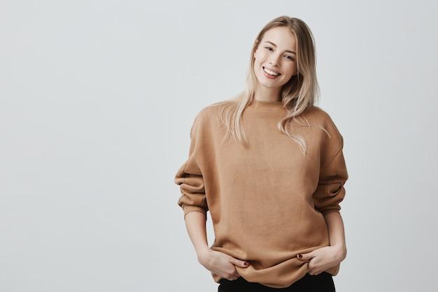 Retrato de mulher jovem em roupas casuais com cabelos loiros tingidos, sorrindo suavemente durante uma conversa agradável, em pé na postura fechada