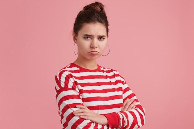 Retrato de mulher jovem emocionada com uma expressão triste no rosto, lábio inferior torto com um olhar descontente, sente-se decepcionada, usa manga comprida listrada, braços cruzados, isolada sobre parede rosa.