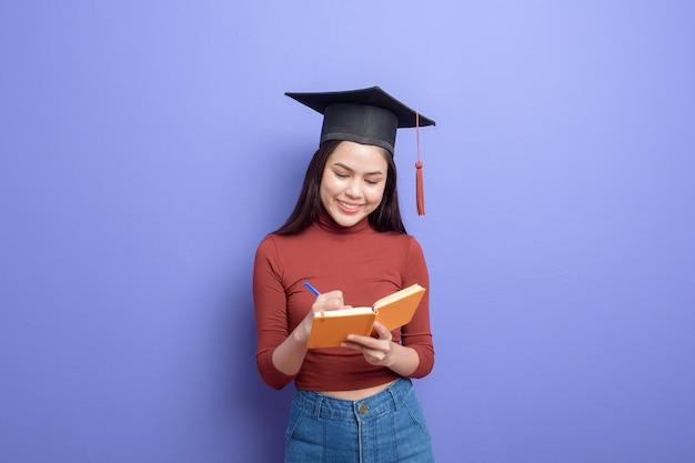 Retrato de mulher jovem estudante universitário com chapéu de formatura em violeta