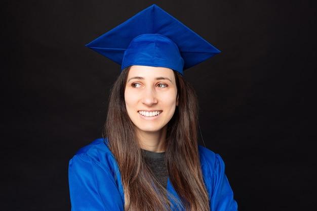 Retrato de mulher jovem estudante vestindo túnica azul e boné de formatura