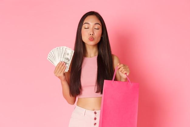 Retrato de mulher jovem expressiva com sacolas de compras e dinheiro