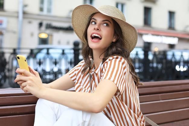 Retrato de mulher jovem, fazendo selfie pelo telefone, sentado no banco na rua da cidade.