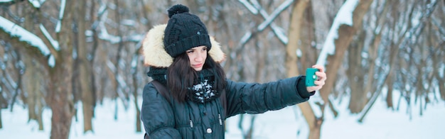 Retrato de mulher jovem fazendo selfie, sorrindo feliz, em winterorest