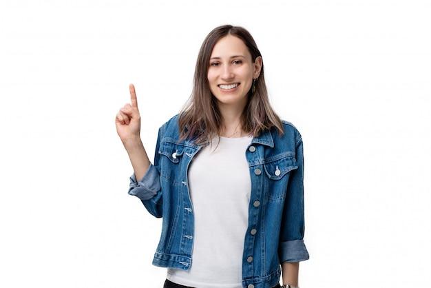 Retrato de mulher jovem feliz, apontando para cima, sobre fundo branco