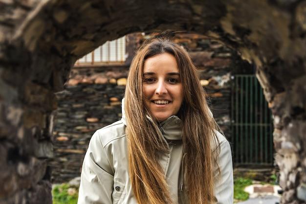 Retrato de mulher jovem feliz através de uma janela de pedra