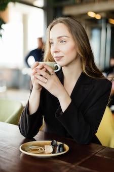 Retrato de mulher jovem feliz com a caneca nas mãos, bebendo café pela manhã no restaurante