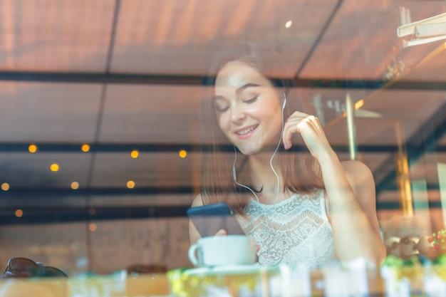 Retrato de mulher jovem feliz com caneca nas mãos, bebendo café no restaurante