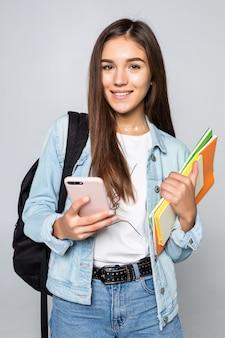 Retrato de mulher jovem feliz, de pé com a mochila, segurando livros e telefone celular isolado na parede branca
