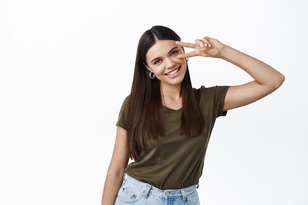 Retrato de mulher jovem feliz, mantendo-se positivo, mostrando o sinal v no olho e dentes brancos sorrindo, encostado na parede do estúdio