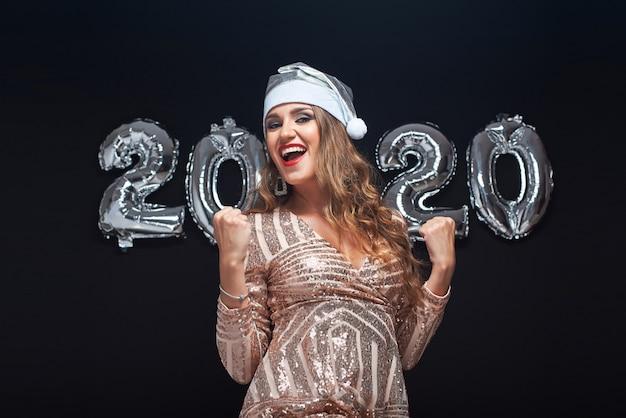 Retrato de mulher jovem feliz no chapéu de papai noel mostrando sim gesto.