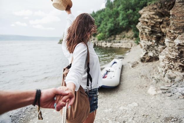 Retrato de mulher jovem feliz no chapéu, segurando o homem à mão e indo para o barco no lago nas montanhas