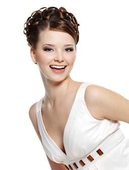 Retrato de mulher jovem feliz rindo com um lindo penteado enrolado