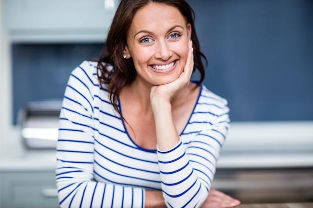 Retrato de mulher jovem feliz, sentado à mesa na cozinha