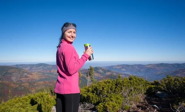 Retrato, de, mulher jovem, hiker, com, xícara chá