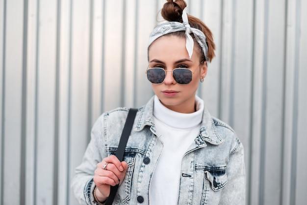 Retrato de mulher jovem hippie em óculos de sol da moda com um penteado elegante em uma camisola vintage branca de malha em uma jaqueta jeans com uma mochila preta perto de uma parede de metal. garota americana moderna.
