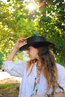 Retrato de mulher jovem hippie no parque da cidade, dia de sol, chapéu preto de couro