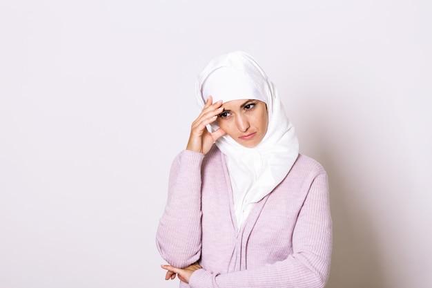 Retrato de mulher jovem infeliz com dor de cabeça. retrato de mulher jovem e bonita muçulmana com ombros nus, tocando seus templos, sentindo o estresse