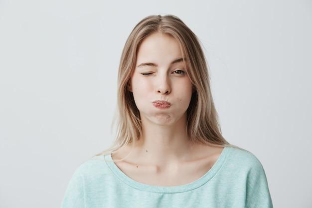 Retrato de mulher jovem loira franzindo a testa, fazendo beicinho nas bochechas, piscando