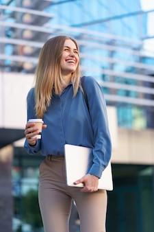 Retrato de mulher jovem loira sorridente segurando laptop e café, vestindo uma camisa azul suave em um prédio moderno