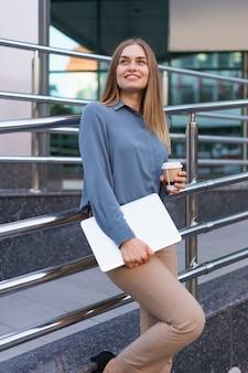 Retrato de mulher jovem loira sorridente segurando laptop e café, vestindo uma camisa azul suave sobre o fundo do edifício moderno