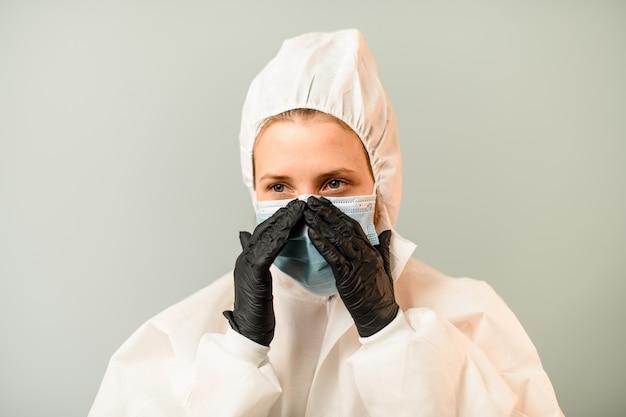 Retrato de mulher jovem médico em traje de proteção branco com capuz que corrige a máscara cirúrgica no rosto.