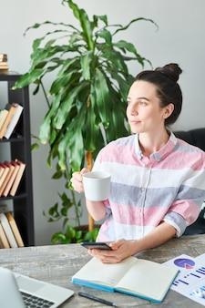 Retrato de mulher jovem moderna, desfrutando de café enquanto trabalha em casa, copie o espaço