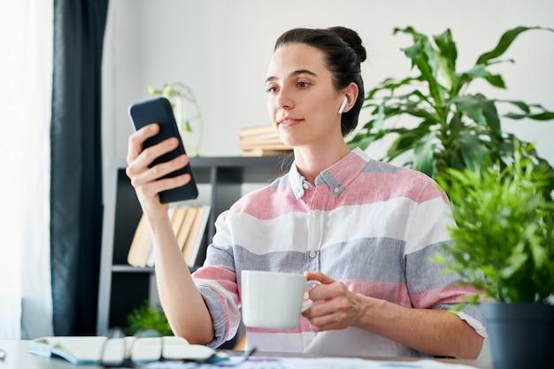 Retrato de mulher jovem moderna usando smartphone no local de trabalho e tomando café, copie o espaço